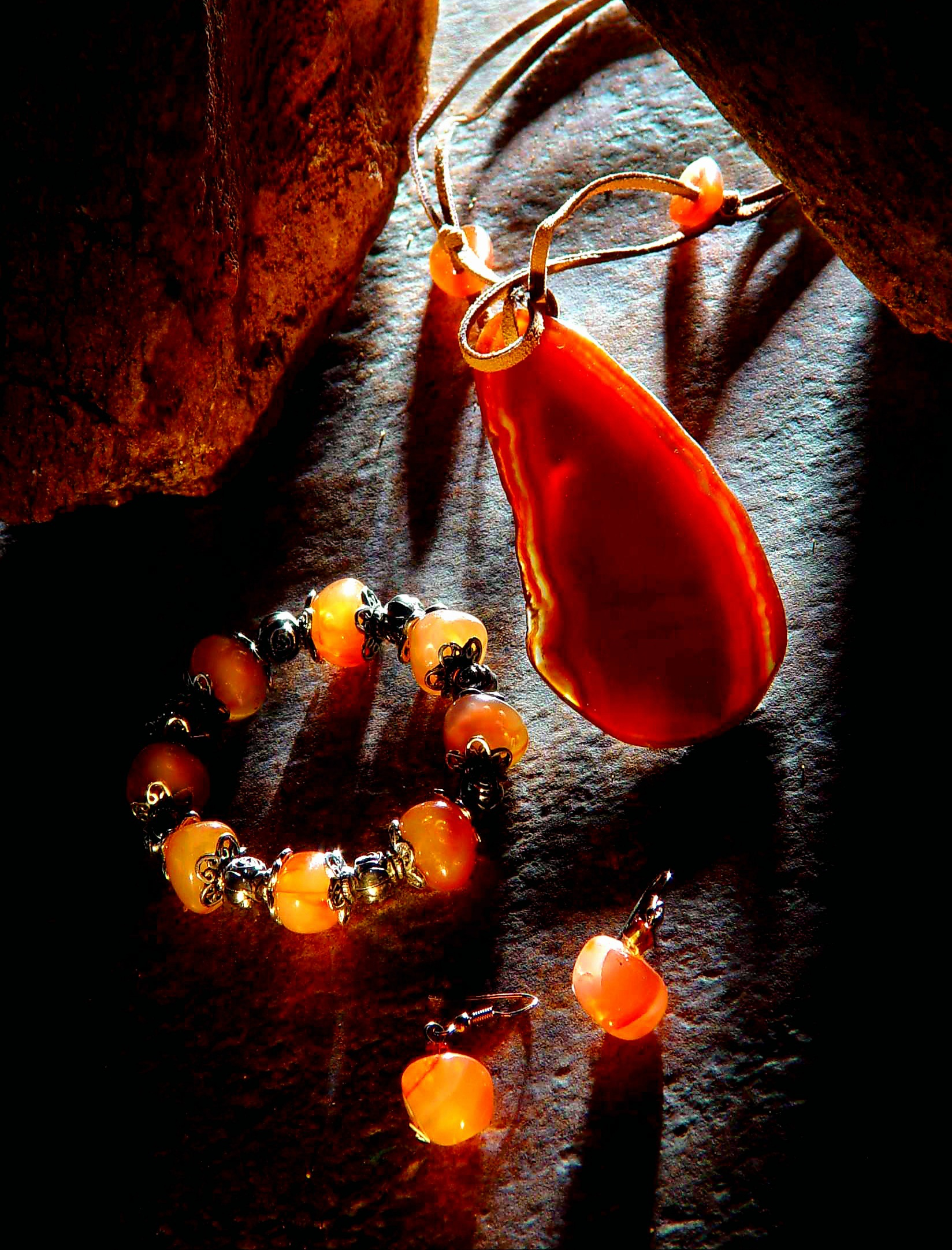 Precious stone pendant and earring jewellery with dramatic lighting for advertising